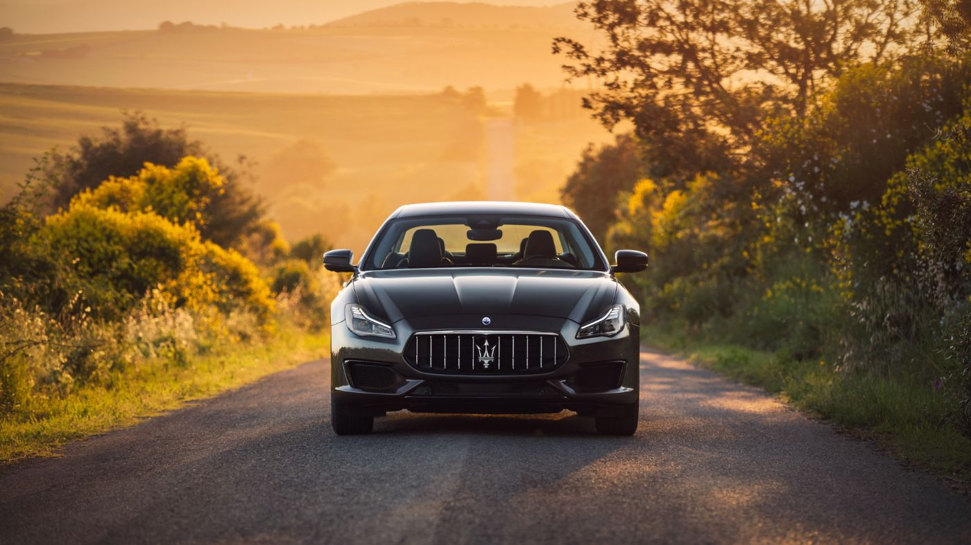 Maserati Quattroporte front view, on a country road at sunset